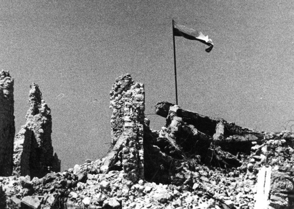 the polish flag being raised over monte cassino